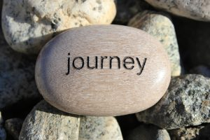 "Photo of a rock with the word ""Journey"" printed on top of it, sitting on a bed of other rocks. Sign of starting your journey in social skills group for Asperger's adults for adults in the San Francisco South Bay Area."