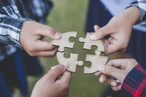 4 hands holding puzzle pieces that fit together to show how social skills groups at Open Doors Therapy can help people with autism connect with one another in the Bay Area.