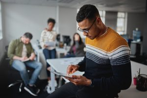 Young professional in striped sweater looking at tablet in a meeting at a tech company | Social Skills for autism in the workplace | Open Doors Therapy | 94306