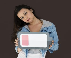 Palo Alto Business Professional Woman looking exhausted, holding low battery symbol | Social Skills in the Workplace- smiling and autism spectrum or aspie adults | Open Doors Therapy | 94306