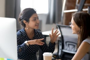 Two female co-workers talking at work | counseling for autistic adult in palo alto, ca | Social skills in the workplace | Social skills classes in Palo Alto, CA | Social Skills Support group in Silicon Valley | Open Doors Therapy | 94306