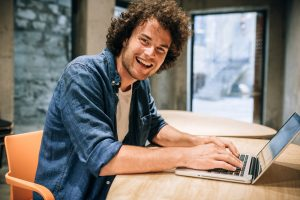 Portrait Of Happy Young Aspie Man on his laptop in Silicon Valley workplace | Social Skills in the Workplace | Open Doors Therapy | Palo Alto CA 94306