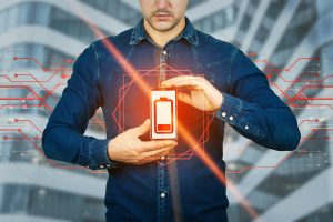 Man holding a red battery illustrating low social battery for young adults with aspergers in Silicon valley| autism therapy south bay area | Social Skills in the Workplace | Open Doors Therapy | Palo Alto 94306