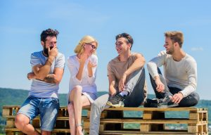 young adults sitting on the beach laughing and smiling after attending a social skills group for young adults in Palo Alto, CA at Open Doors Therapy 94306