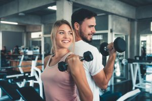 Neurodiverse autistic couple working out at the gym. One partner attended a social skills group for high functioning autistic adults in Palo Alto, CA at Open Doors Therapy
