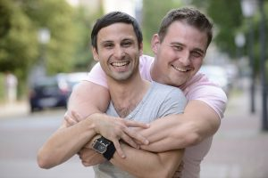 gay neurodiverse couple hugging on the street in the south bay area after learning about date ideas for neurodiverse adults and autistic adults and attending an autism social skills group in Palo Alto, CA 94306 at Open Doors Therapy