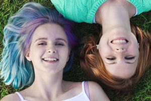 Autistic adult women in a relationship laying in the grass looking at the camera. Lesbian, gay, bisexual dating for neurodiverse adults can be hard but Autism resources in Palo Alto, CA 94306 and social skills groups for adults with autism are available at Open Doors Therapy