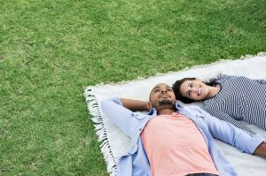 young couple laying on a blanket in the grass. One partner has aspergers and attends a social skills group for autistic adults in Palo Alto, CA 94306 at Open Doors Therapy