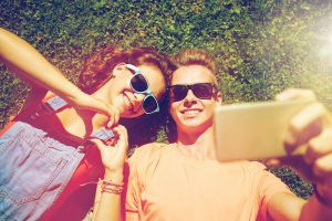 neurodiverse couple laying in the grass taking a selfie. dating for neurodiverse adults can he challenging but autism therapy services and social skills groups in in Palo Alto, CA 94306 at Open Doors Therapy can help!