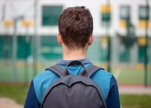 gifted teen with autism wearing a backpack at school before going to autism social skills class in Palo Alto at Open Doors Therapy. Parents and caregivers can get help in asperger teen counseling palo alto, ca and online therapy in California