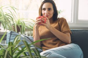 Sitting on her couch, a woman with autism is enjoying a cup of coffee at home. She has learned new social skills in the women's autism support group in Palo Alto, CA 94306 at Open doors therapy