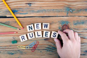 "Image of scrabble tiles saying ""new rules"" on a table with school supplies representing the need for new rules in autism families during covid-19. Learn more tips in an online autism parent support group in California from Open Doors Therapy, specializing in online autism therapy in California"