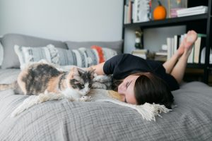 teen with autism lays on her bed and pets her cat during the coronavirus pandemic. She receives online autism therapy in california with Open Doors Therapy