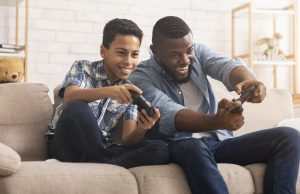 Autism parent plays video games with his autistic teen. He learns useful tips form an online autism parent support group in California with Open Doors Therapy, specializing in online autism therapy in California