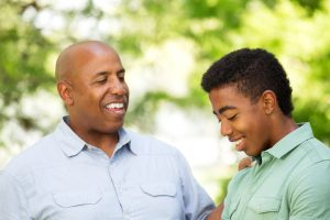 happy dad and teen with autism smile outdoors in California. They attend online group therapy and an autism parent support group with open doors therapy in california