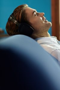 teen with autism relaxes with headphones on. he attends online group therapy in CA with others teens with autism at Open Doors Therapy