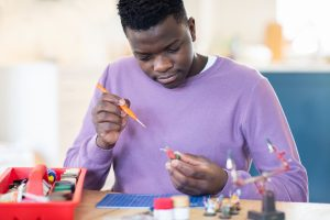 male teen with autism putting model figures. He attends a social skills group for twice-exceptional teens in palo alto, ca at open doors therapy 94306