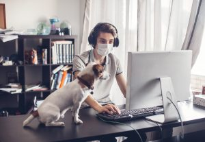 teen with autism wears a mask while working on his computer at home during the covid-19 pandemic. He goes to online group therapy in California with Open Doors Therapy and learns social skills. Autism resources in Palo Alto, CA can also be found online