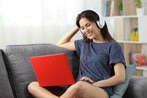 Girl wearing headphones smiles while attending group therapy from her couch. She gets online group therapy in California with Open Doors Therapy who provides social skills groups for autistic adults and neurodiverse teens with online autism therapy in california
