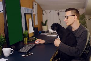 young adult with autism holds his dog during online autism therapy in California with Open Doors Therapy and an autism therapist