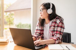 teen with autism wearing headphones looks out the window before logging into online autism therapy in California with Open Doors Therapy and an autism therapist