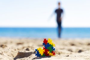 child running on the beach in the background and an autism puzzle piece heart in the foreground. Begin online autism therapy in California and an online autism parent support group with Open Doors Therapy