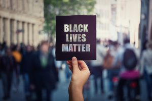 protester holds up a sign that reads Black Lives Matter at a rally. Autism Therapist Tasha Oswald discusses the BLM movement and how it relates to neurodiversity. Learn more at Open Doors Therapy 94306