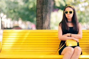 woman with autism sits on a yellow park bench looking upset. Read more about dating on the autism spectrum from a therapist at Open Doors Therapy 94306