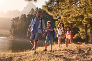 happy family hiking outdoors. They got autism family therapy in California to deal with their challenges and worked with an autism therapist from Open Doors Therapy