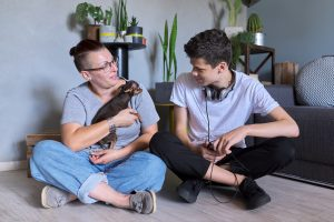 happy mom and teen boy with their dog after autism family therapy with an autism therapist in California at Open Doors Therapy