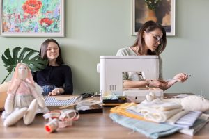 Mom and teen daughter spending quality time together sewing. They got autism family therapy in California with an autism therapist at Open Doors Therapy