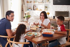 happy family eats dinner together. They get autism family therapy in California with an autism therapist at Open Doors Therapy 94306