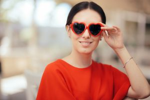 woman with heart shaped sunglasses looks at the camera smiling after offering herself self-compassion to overcome the hardships of autism and loneliness.