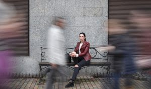 lonely woman in a crowd sits on an outdoor bench representing the pain and loneliness many individuals with autism experience. Learn more about making friends on the autism spectrum from an autism therapist who offers online autism therapy in California