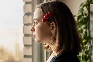 sad woman with heart hair clips looks out the window. She is dealing with autism and loneliness after having trouble navigating dating on the autism spectrum. She gets online autism therapy in California with Open Doors Therapy