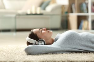 woman wears headphones and listens to music while lying on the floor. She gets support for autism in women with an autism therapist who offers online autism therapy in California