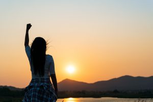 triumphant woman raising her fist up at sunset representing the feeling many women have when a care provider understands autism in women. Get autism therapy in California today.