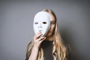 woman covers half her face with a white mask representing masking and autism. Get support for autism in women in California though online autism therapy