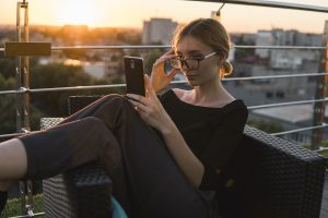 woman in glasses looks at her phone on a rooftop deck. She could be interviewing autism therapists to determine if they understand autism in women. She gets online autism therapy in California