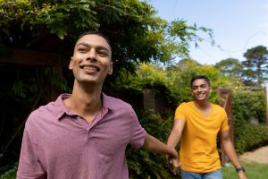 two gay men hold hands outdoors smiling. This represents dating on the autism spectrum after getting support from an autism therapist who offers online autism therapy in California
