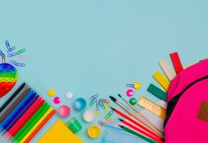 photo of colorful school supplies against a blue background representing going back to school. Get an autism therapist's tips for avoiding autism burnout.